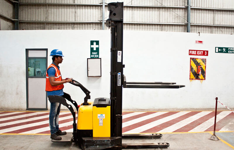 Worker with fork lift in a warehouse