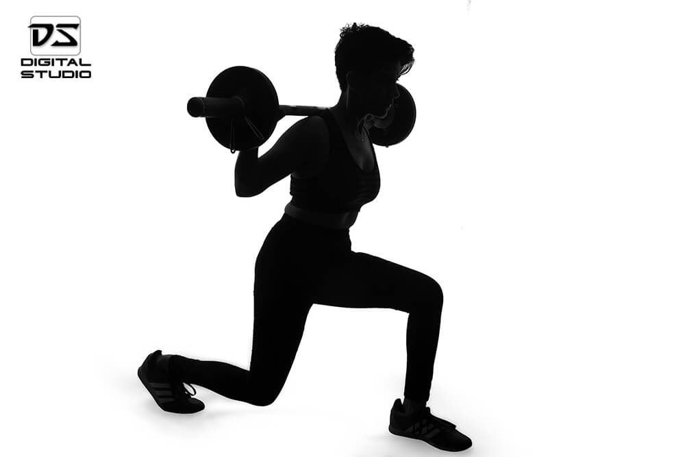 female fitness model doing barbell lunges