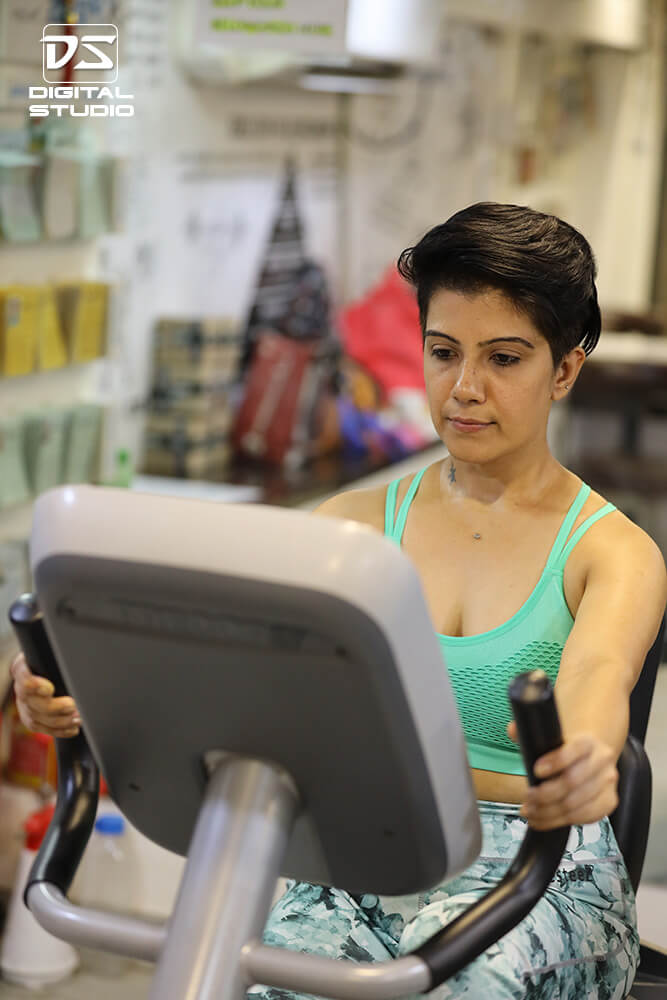 Lady fitness model doing cadio on stationary bike