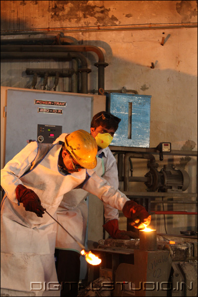 Workers with molten metal equipment