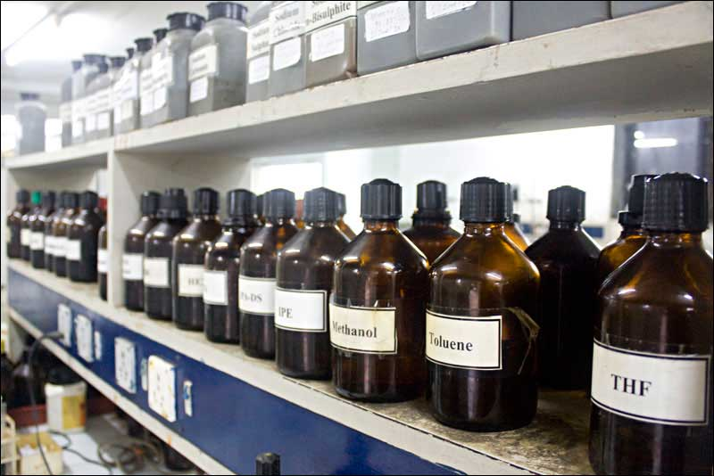 Rows of chemical bottles in a lab