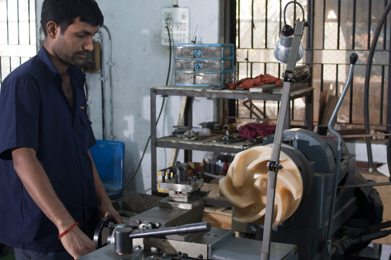 Worker working on a pump making machine