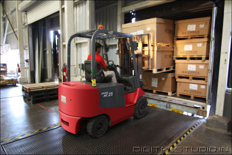 photograph of a worker in a red forklift