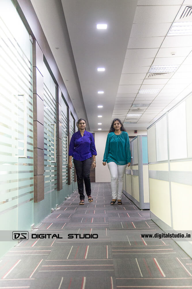 two lady office staff walking in office