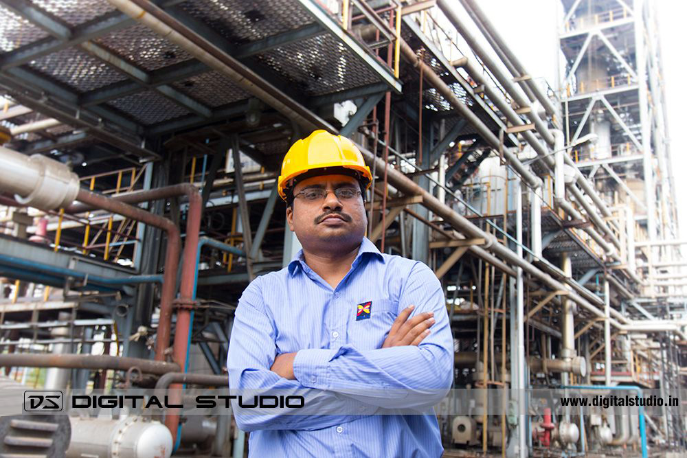 Worker posing in front of refinery plant