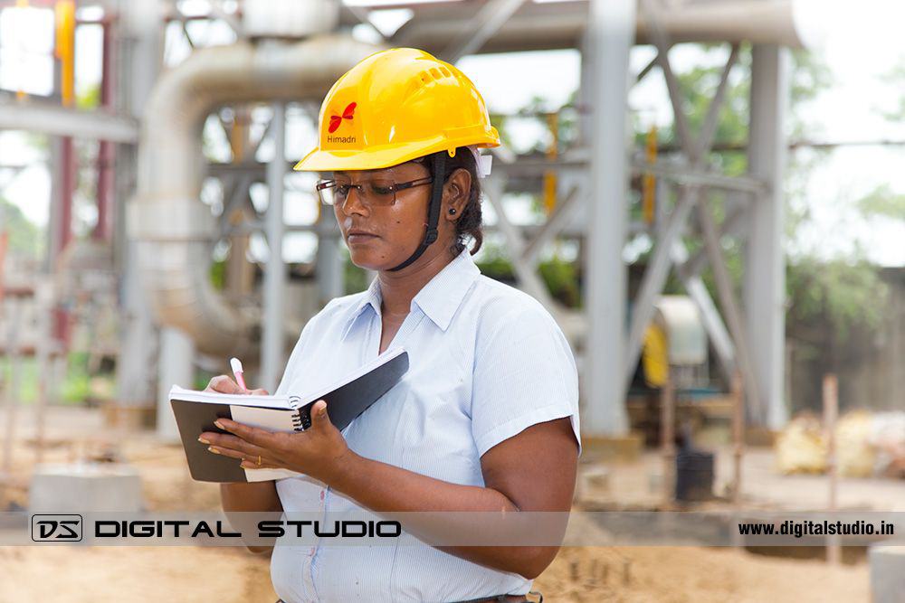 Lady engineer making notes in factory