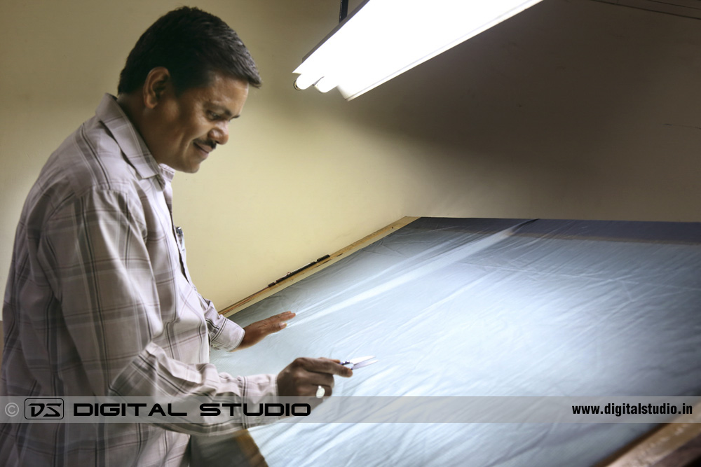 Glass table with worker checking fabric quality