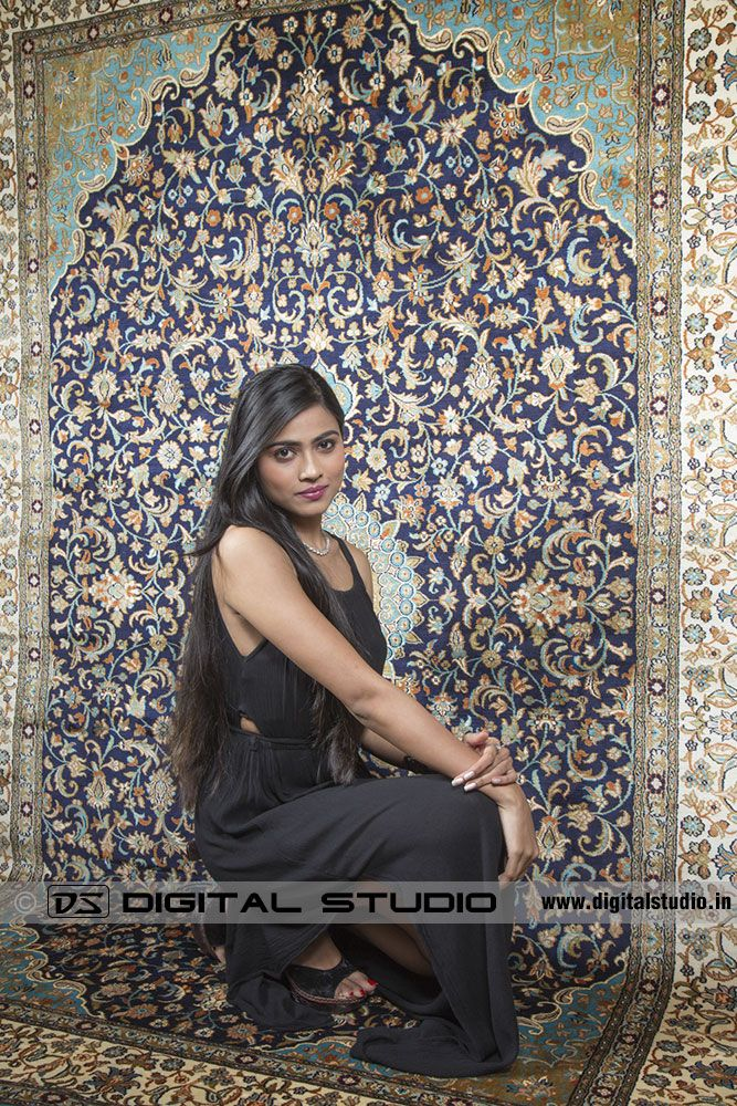 Model posing next to oriental carpet