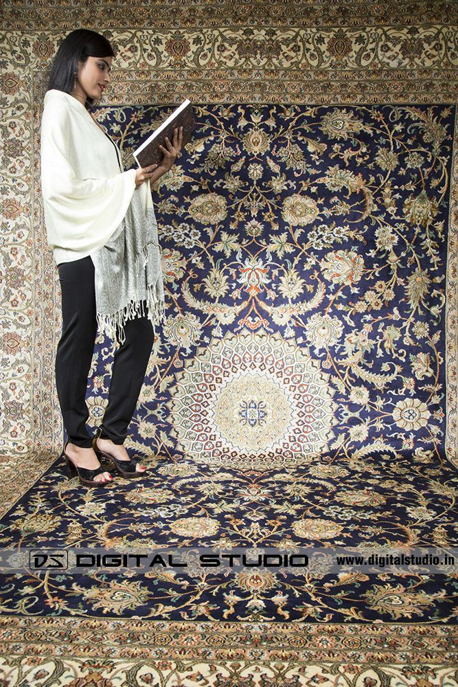 model reading a book on Kashmir carpet