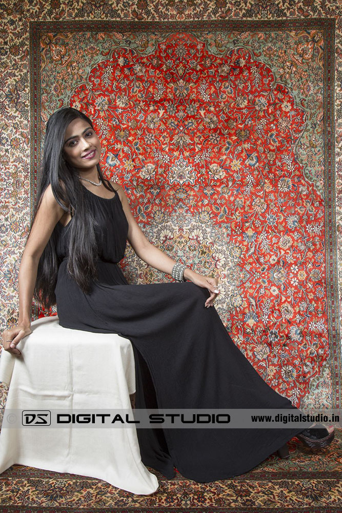 Model sitting on stool with handmade rug