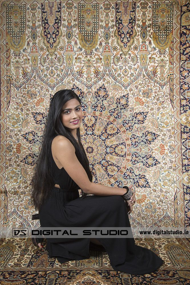 Model sitting in front of oriental rug