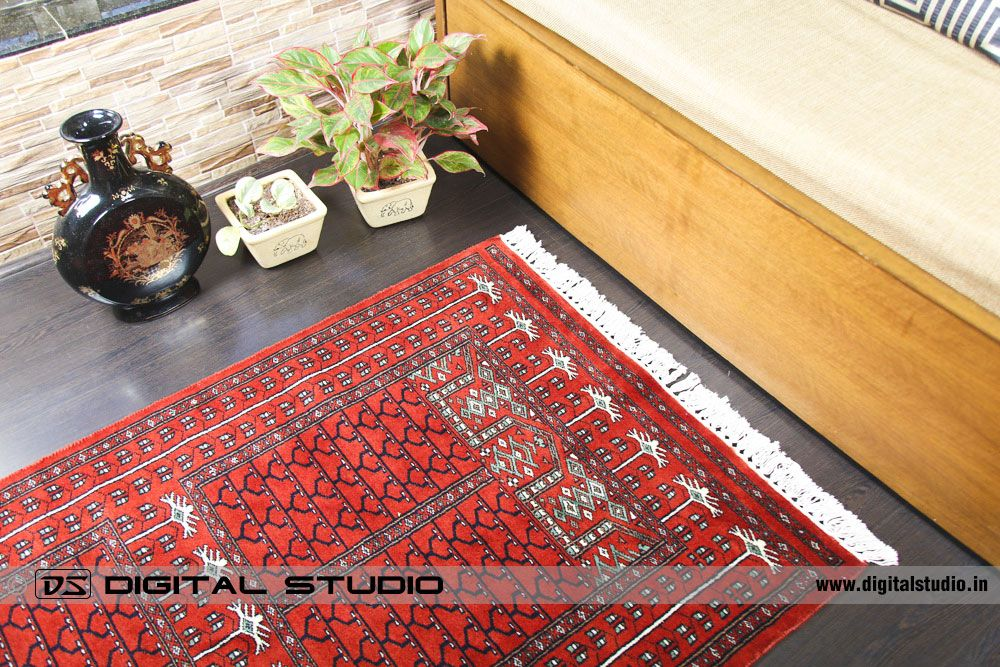 Red oriental carpet on wood flooring