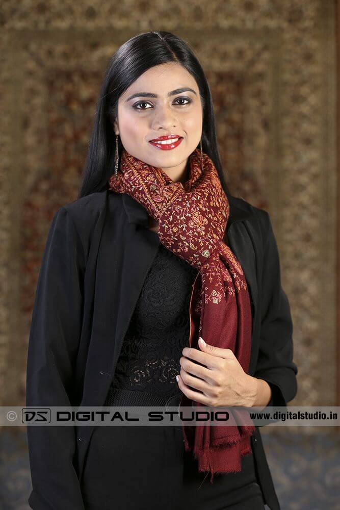 Embroidered shawl draped around model's neck